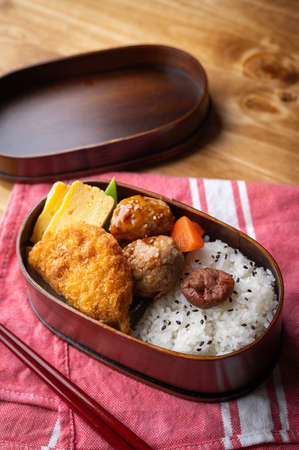 japanese style bento in wooden box with meat ball and croquette 免版税图像