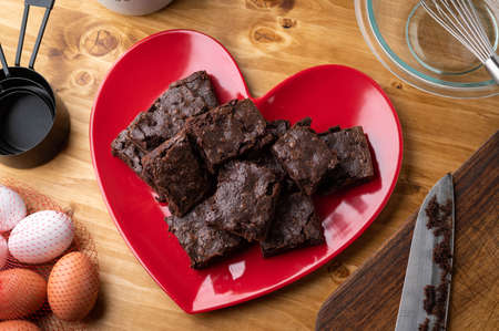 Chocolate brownies on red heart shaped dish