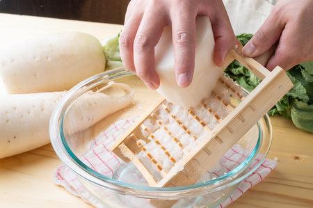 Grating daikon radish with traditional japanese bamboo grator