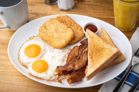 american breakfast with egg, bacon, hash brown and toast