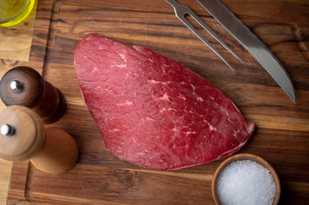 raw flank steak on wooden cutting board