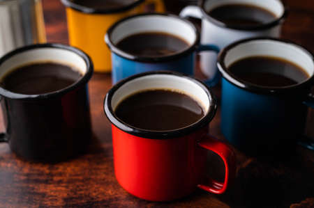 coloful enameled mug with coffee on dark wooden table