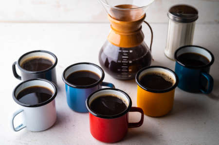 coffee in many colorful mugs on white background