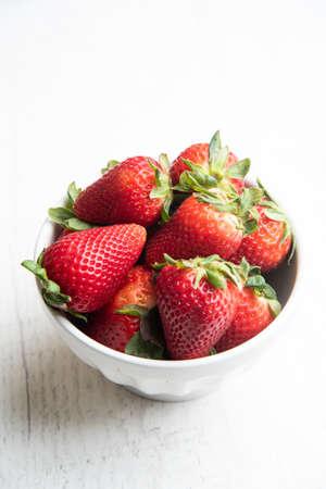 strawberry in white bowl on white background