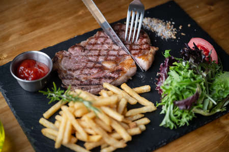 cutting steak with knife and fork on black plate