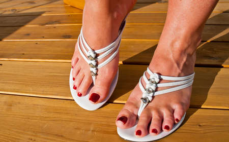 A lady displays her newly pedicured feet in sandals