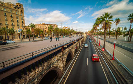 guardrails: People and traffic in the city streets of coastal Barcelona on a warm autumn afternoon.