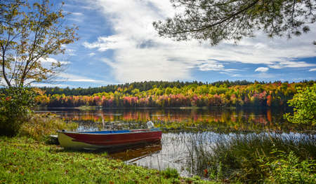 A red fishing boat amongst the water reflected colors of late September.