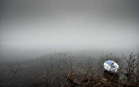 unloved: Unloved Beach Ball left abandoned.  A cold November morning for a forgotten old beach ball on the shoreline of a lake in Ontario Canada.