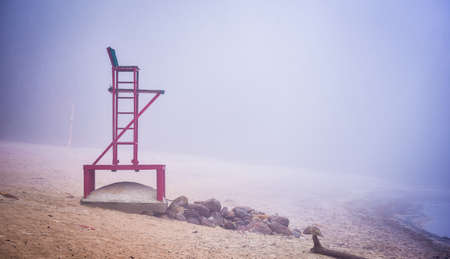 Empty beach lifeguard chair - a lonely lifeguard seat stands empty in fog on a November beach in Ontario Canada.