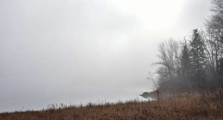 obscured: Heavy fog with diffused bright sunlight on Ottawa River.  Rapidly changing dense fog envelopes the bay - obscured sunshine beaming through fog, bright diffusion, mid-morning sunrise. Stock Photo