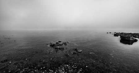 enveloping: Rocks like islands protruding from Ottawa River shoreline shrouded in dense fog. Stock Photo