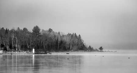 enveloped: Black and white of Fog shrouding peninsular forest - mist rising from blue.  Dense blanket of fog lifting off the Ottawa River revealing a small peninsular forest and lighthouse, Ontario Canada.