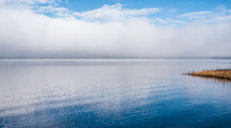 receding: Fog rising from blue - Receding fog line on the Ottawa River - horizontal divide of two environments - air and water creates a visual spectacle.  Split blue horizon.  Blanket of fog lifting off the Ottawa River