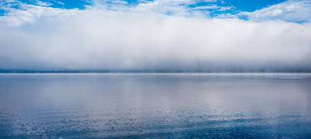 Low cloud on horizon, fog line on Ottawa River - horizontal divide splits two environments - air and water  come together, nature water background.