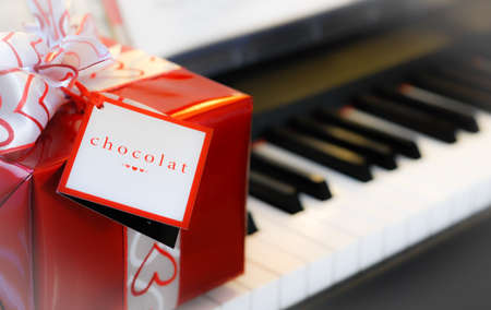 giftwrapped: Giving the gift of chocolate.  A red and white gift box package wrapped in red featuring white ribbon with red hearts, tag that reads:  chocolat - resting on piano keyboard in background.