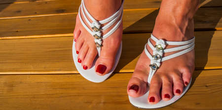 womans: Womans feet in white tri strap summertime sandals, afternoon sun, on new wooden deck.