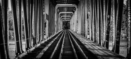 yesteryear: Railway bridge and tracks - single point perspective.    Black and white view down the tracks on an old railway bridge from yesteryear.  Ottawa, Canada. Stock Photo