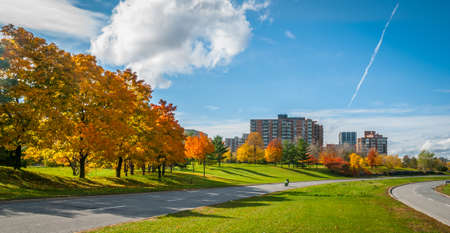 Motorcycle moving down parkway road that follows the Ottawa River.  Apartments and condominium along the parkway - Urban Mechanicsville Ottawa parkway panoramic in clear sunshine.