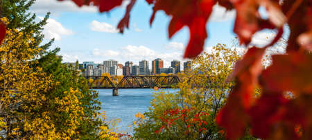 Naturally framed - Prince of Wales railway trestle appears from behind trees, passes over pededstrian walkway along Ottawa River.  Tall buildings, condominiums comprise Ottawa city skyline.  Clear autumn afternoon clouds on horizon hillside view near park Stock Photo
