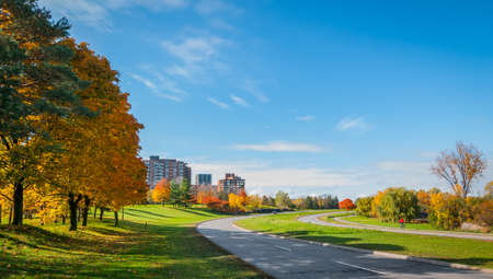 Traffic, cyclist, and runners along Ottawa riverside parkway - winding paved roads make for an outing in autumn afternoon sun. Panoramic view - road follows Ottawa River. Apartments condos along parkway.