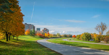Traffic along the riverside parkway - winding paved roads make for an outing in autumn afternoon sun.  Panoramic view - road that follows the Ottawa River.  Apartments  condos along parkway. Stock Photo