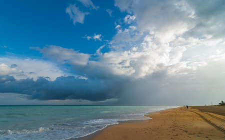 blustery: Blustery rain passes.  Warm ocean waves gently lap against a Cuban beach.  Cloudscape on open beach with waves gently breaking on the shore. Stock Photo