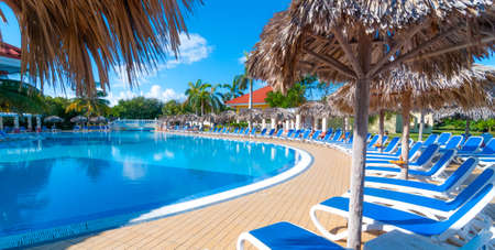 bathers: Beautiful blue sky holiday resort pool side view.  Getaway vacation in Cuba.  Lay back on deck chairs.  People relaxing on holidays at a resort hotel pool side and deck.