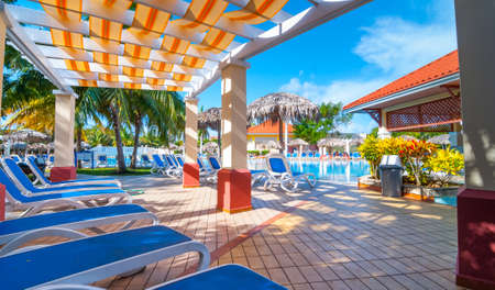 sun bathers: Beautiful blue sky holiday resort pool side view.  Getaway vacation in Cuba.  Lay back on deck chairs.
