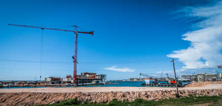 Construction of new hotel and resort. Building goes up. Brand new hotel being built on countryside land. construction crane nearby. Sunshine workday - constructing new hotel resort. Reklamní fotografie