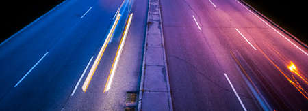 light streaks: Traffic in the night.  Light streaks from passing cars illuminate the pavement.    Traffic travelling over the inter-provincial bridge joining Ontario to Quebec    Ottawa and Gatineau cities.  Streetlights illuminate bridge.