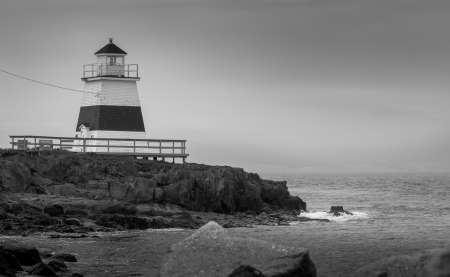 leaden splash: Lighthouse in Margaretsville, Nova Scotia.  Overcast spring day in the Bay of Fundy.  A lone lighthouse atop an outcropping of rock in the Bay on an grey sky, late spring day in Nova Scotia.