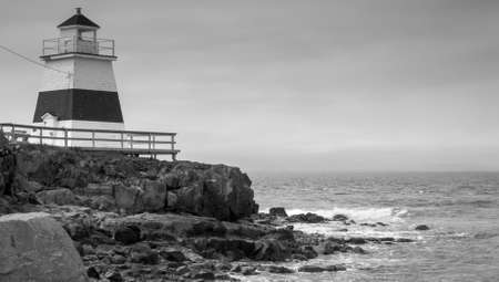 dreary: Lighthouse in Margaretsville, Nova Scotia.  Overcast spring day in the Bay of Fundy.  A lone lighthouse atop an outcropping of rock in the Bay on an grey sky, late spring day in Nova Scotia.