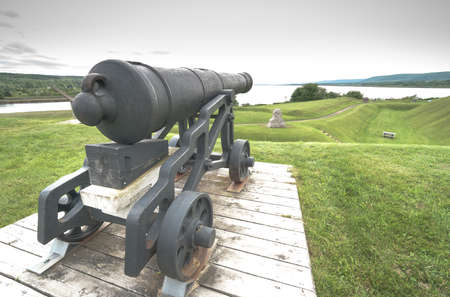 Old guns of yesteryear, a cannon overlooking lands they once defended, from the 18th century, sits on its display platform, never to fire again.  Spring day in Nova Scotia.