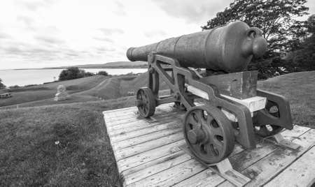 of yesteryear: Old guns of yesteryear, a cannon overlooking lands they once defended, from the 18th century, sits on its display platform, never to fire again.  Spring day in Nova Scotia.
