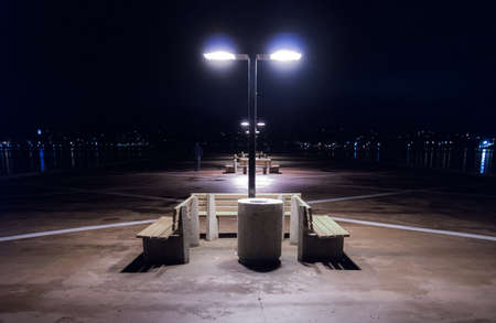 energized: Night on a lonely dock in Halifax, Nova Scotia.  Empty benches and energized lights on a Halifax, Nova Scotia night.  Long Jetty protrudes into the harbor.  City of Halifax at night. Stock Photo