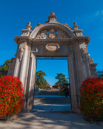 bluesky: Gates to Retiro Park of Madrid, Spain on a blue-sky sunny day.  Citizens of Madrid and tourists alike enjoy a fabulous warm November day in one of the main parks.