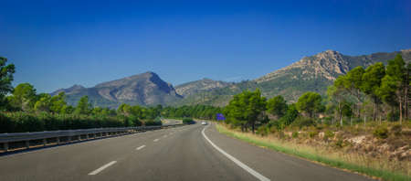 geological feature: Highway through coastal Foothills and mountains of Spain.  Sunshine on Coastal highway running through foothills and mountain ranges on the edges of continental Europe in Spain.