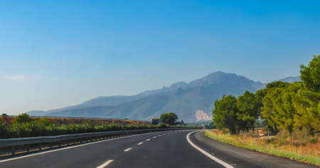 mountain ranges: Highway through coastal Foothills and mountains of Spain.  Sunshine on Coastal highway running through foothills and mountain ranges on the edges of continental Europe in Spain.