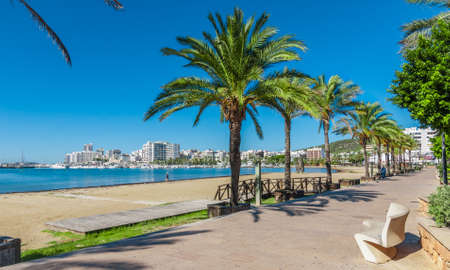 mid morning: Mid morning sun, walk along the beach near the city.  Warm sunny day along the waters edge in Ibiza, St Antoni de Portmany Balearic Islands, Spain - city by the bay, row of palms lines the beach. Stock Photo
