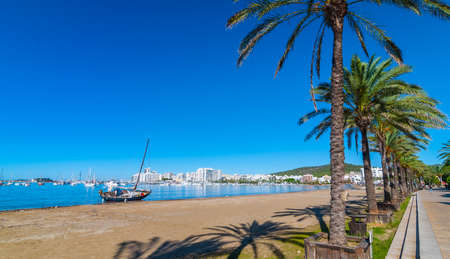 mid morning: Mid morning sun, walk along beach near the city sees an abandoned sailboat.  Rows of palm trees line the beach, sunny day along the waters edge in Ibiza, St Antoni de Portmany Balearic Islands, Spain. Stock Photo