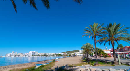 mid morning: Mid morning sun on Ibiza waterfront.  Warm sunny day along the beach in St Antoni de Portmany Balearic Islands, Spain