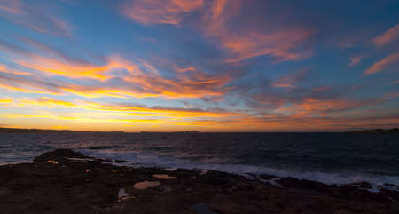 blustery: Golden sunset behind Conejera Islands.  Choppy waters of Balearic sea churns waves on rocks along shore.   View of Conejera Islands from behind cafe del mar in Ibiza in November. Stock Photo