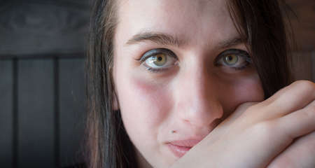 millennial: Generic portrait of young woman looking serenely at camera.  A beautiful young woman, appears to be pondering something while she looks at the camera.   Young millennial girl with Auburn green eyes and brunette hair.