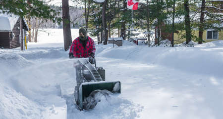 blustery: A Canadian man operating a snow throwing machine on a winter day after a snowstorm dumped 8 inches of snow.  Man operating a snow blower in Canada.