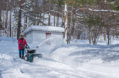 dumped: A Canadian man operating a snow throwing machine on a winter day after a snowstorm dumped 8 inches of snow.  Man operating a snow blower in Canada.