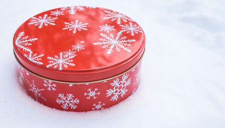 Red, round cookie & baked goods tin container decorated in red with white snowflake print pattern, sitting in natural snow.