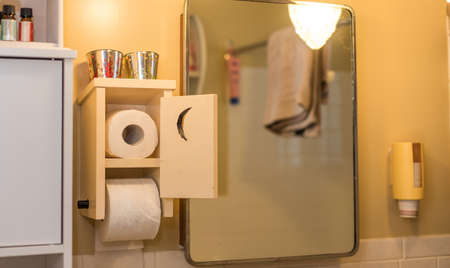 Wooden toilet paper holder with crescent moon cut into door, toilet paper inside and one roll on spool.  Essential needs, Even in the bathroom, paperwork is never done.