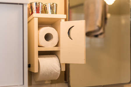 Wooden toilet paper holder with a little door, crescent moon cut into door, toilet paper inside and one roll on spool.  Essential paper needs in a bathroom.   Low angle partial view of bathroom, mirrored light, towel on a shower curtain bar.