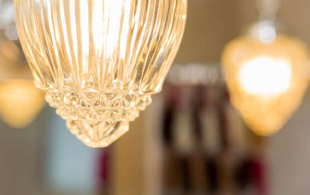 home lighting: Detail of a crystal style glass cover which adorns a hanging chain link, swag style lamp in a bathroom.  Fashionable lighting for the home. Stock Photo